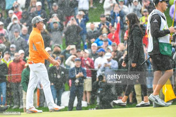 Rickie Fowler and his fiancee Allison Stokke meet on the eighteenth hole green after the final round of the Waste Management Phoenix Open at TPC...