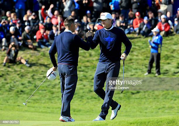 Rickie Fowler and Jimmy Walker of the United States celebrate halving their match during the Morning Fourballs of the 2014 Ryder Cup on the PGA...