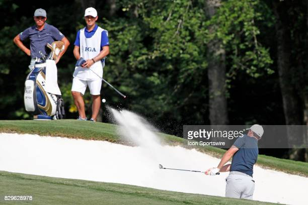 Rickie Fowler and McIlroy's caddie Harry Diamond watch Rory McIlroy hit out of a sand trap on the 12th hole during the first round of the PGA...