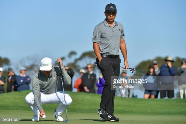 Rickie Fowler and Xander Schauffele look over their putts on the 11th hole during the first round of the Farmers Insurance Open at Torrey Pines on...