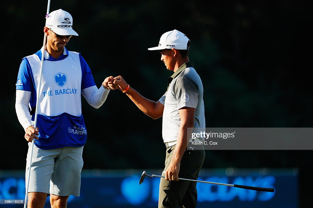 Rickie Fowler celebrates with his caddie Joe Skovron on the 18th green after a three-under par 68 during the third round of The Barclays in the PGA Tour FedExCup Play-Offs on the Black Course at Bethpage State Park on August 27, 2016 in Farmingdale, New York.