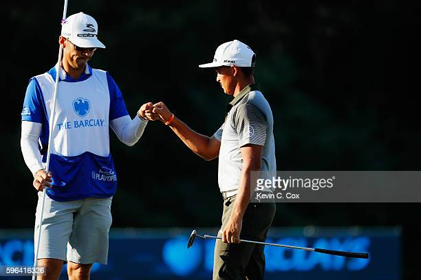 Rickie Fowler celebrates with his caddie Joe Skovron on the 18th green after a threeunder par 68 during the third round of The Barclays in the PGA...