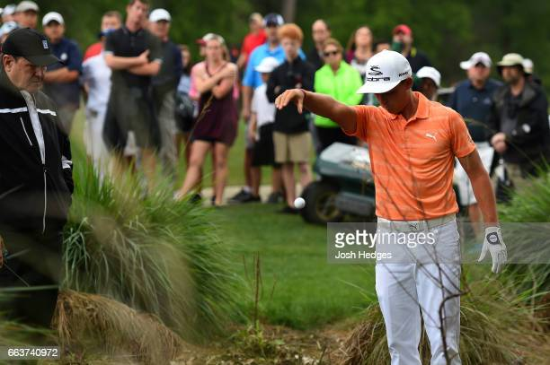 Rickie Fowler drops his ball after it was embedded in the deep rough on the second hole during the final round of the Shell Houston Open at the Golf...