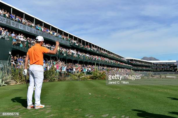 Rickie Fowler encourages the crowd prior to playing his tee shot on the 16th hole during the final round of the Waste Management Phoenix Open at TPC...