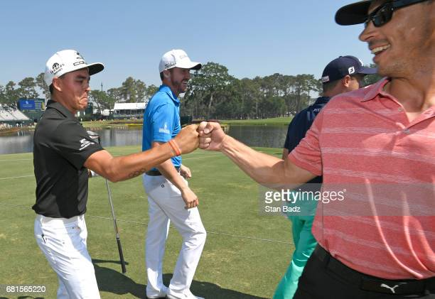 Rickie Fowler highfives his caddie Joe Skovron after making a hole in one on the 17th hole during the Dreams Come True Inside The Ropes Caddie...