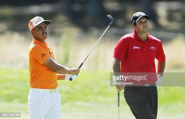 Rickie Fowler hits a shot on the fourth hole as Patrick Reed looks on during the final round of The Barclays in the PGA Tour FedExCup PlayOffs on the...