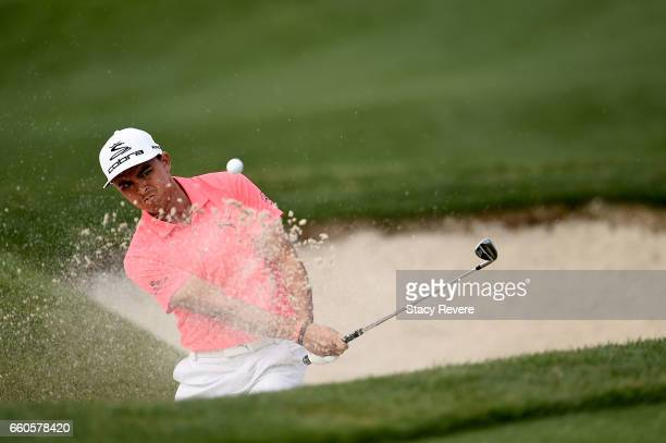 Rickie Fowler hits his third shot from a greenside bunker on the 15th hole during the first round of the Shell Houston Open at the Golf Club of...