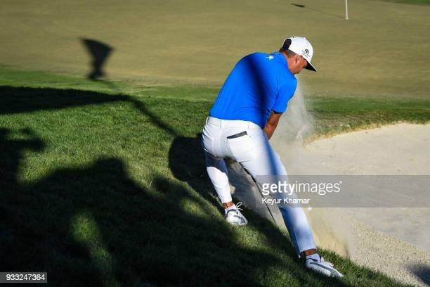 Rickie Fowler hits his third shot from a plugged lie in a bunker on the 18th hole during the third round of the Arnold Palmer Invitational presented...