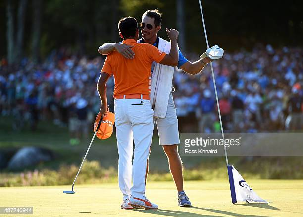 Rickie Fowler hugs his caddie Joe Skovron following his one stoke victory in the final round of the Deutsche Bank Championship at TPC Boston on...