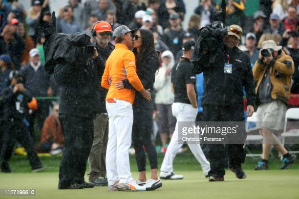 Rickie Fowler is met and congratulated by his fiancé Allison Stokke on the 18th green after winning the Waste Management Phoenix Open at TPC...