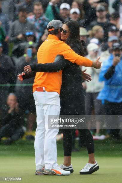 Rickie Fowler is met and congratulated by his fiancé Allison Stokke after winning in the final round of the Waste Management Phoenix Open on February...