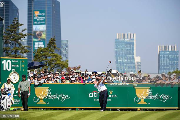 Rickie Fowler of Team USA tees off as fans watch on the 10th hole during the first round of The Presidents Cup at Jack Nicklaus Golf Club Korea on...