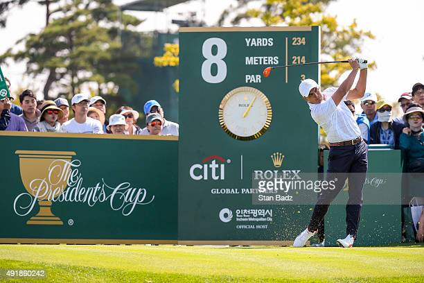 Rickie Fowler of Team USA tees off on the eighth hole as fans watch during the first round of The Presidents Cup at Jack Nicklaus Golf Club Korea on...