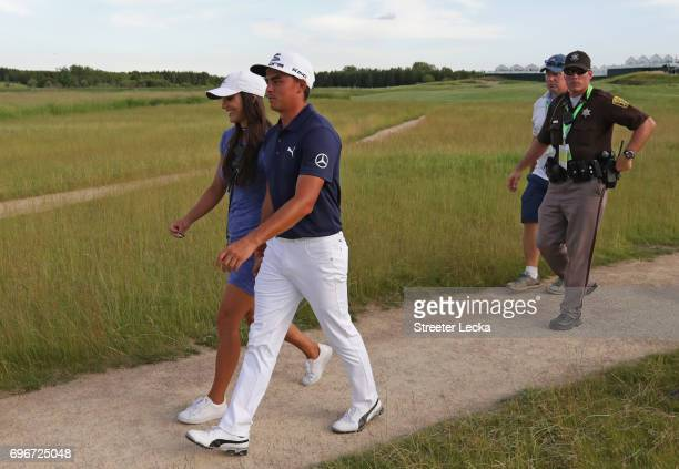 Rickie Fowler of the United States and Allison Stokke walk off the course during the second round of the 2017 US Open at Erin Hills on June 16 2017...