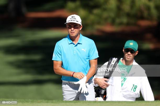 Rickie Fowler of the United States and caddie Joe Skovron walk to a green during a practice round prior to the start of the 2017 Masters Tournament...