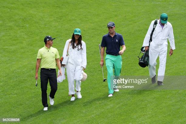 Rickie Fowler of the United States and girlfriend Alison Stokke Justin Thomas and his father Mike Thomas walk together during the Par 3 Contest prior...