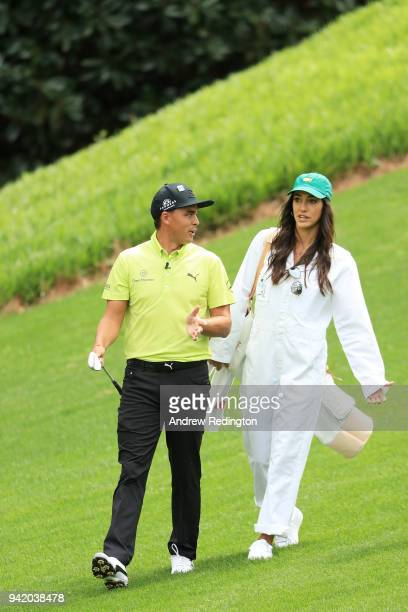 Rickie Fowler of the United States and girlfriend Alison Stokke walk together during the Par 3 Contest prior to the start of the 2018 Masters...