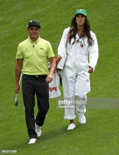 Rickie Fowler of the United States and girlfriend Allison Stokke walk together during the Par 3 Contest prior to the start of the 2018 Masters...