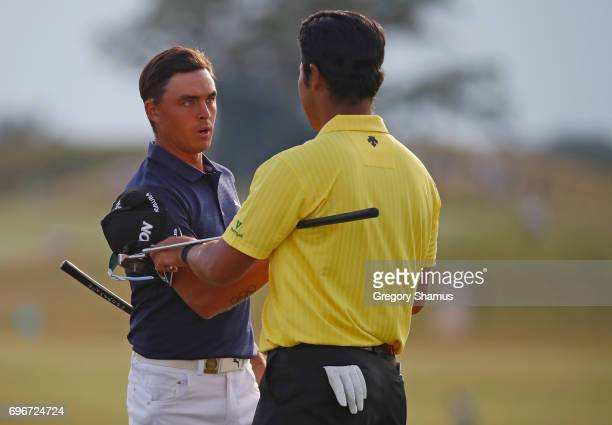 Rickie Fowler of the United States and Hideki Matsuyama of Japan meet after finishing on the 18th green during the second round of the 2017 U.S. Open...