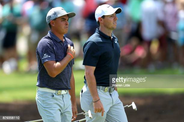 Rickie Fowler of the United States and Rory McIlroy of Northern Ireland walk along the second hole during the first round of the 2017 PGA...