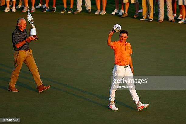 Rickie Fowler of the United States celebrates victory as he walks to collect the winners trophy after round four of the Abu Dhabi HSBC Golf...