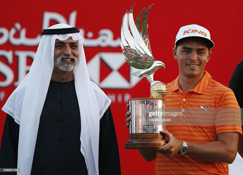 Rickie Fowler of the United States celebrates with his trophy after winning in the final of the Abu Dhabi Golf Championship in the capital of the United Arab Emirates on January 24, 2016. Fowler opened up a two-shot lead following a 65 in his third round that was eventually completed in the morning, and then shot a three-under par 69 for a 16-under par total. / AFP / KARIM