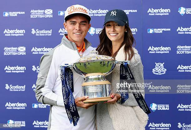 Rickie Fowler of the United States celebrates with the trophy alongside his girlfriend, Alexis Randock, after winning the Aberdeen Asset Management...