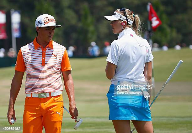 Rickie Fowler of the United States chats with LPGA player Jessica Korda on the practice ground during the final round of the 114th US Open at...