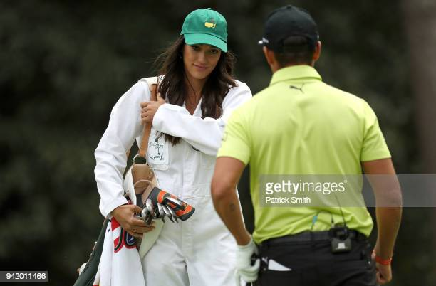 Rickie Fowler of the United States chips to a green as his girlfriend Allison Stokke looks on during the Par 3 Contest prior to the start of the 2018...
