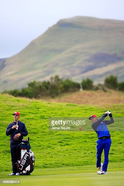 Rickie Fowler of the United States hits a fairway wood with caddie Joe Skovron during practice ahead of the 2014 Ryder Cup on the PGA Centenary...