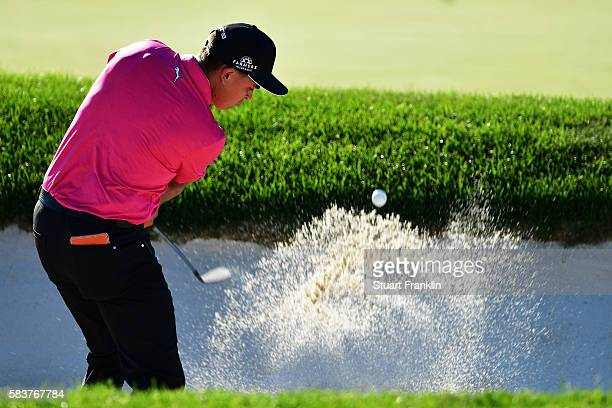 Rickie Fowler of the United States hits a shot from a bunker during a practice round prior to the 2016 PGA Championship at Baltusrol Golf Club on...