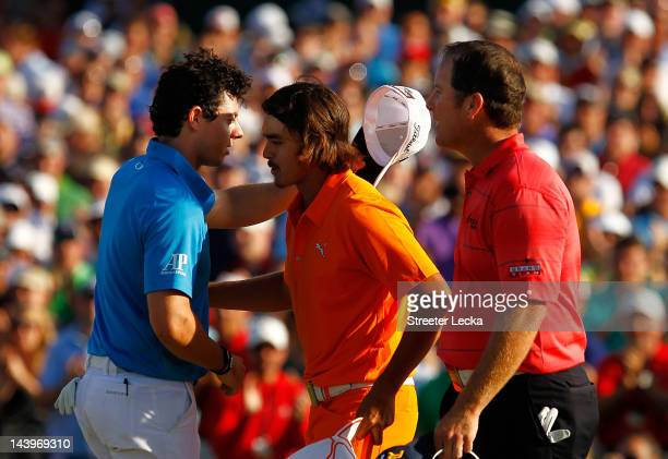 Rickie Fowler of the United States is congratulated by Rory McIlroy of Northern Ireland and D.A. Points of the United States after making a putt for...