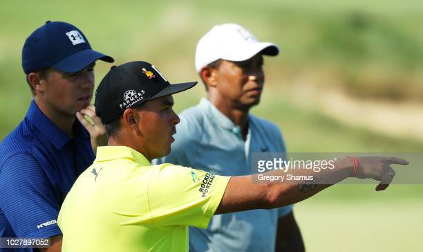 Rickie Fowler of the United States Jordan Spieth of the United States and Tiger Woods of the United States talk during the first round of the BMW...