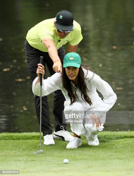 Rickie Fowler of the United States lines up a putt with girlfriend Allison Stokke during the Par 3 Contest prior to the start of the 2018 Masters...