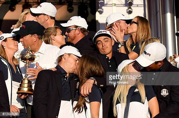 Rickie Fowler of the United States looks on while fellow team members celebrate with their partners at Hazeltine National Golf Club on October 2,...
