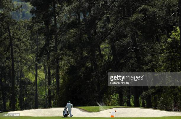 Rickie Fowler of the United States plays a shot from a bunker on the second hole as caddie Joseph Skovron looks on during the final round of the 2018...