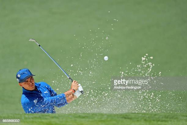 Rickie Fowler of the United States plays a shot from a greenside bunker on the second hole during the second round of the 2017 Masters Tournament at...