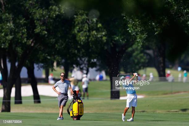 Rickie Fowler of the United States plays a shot on the eighth hole as his caddie Joe Skovron looks on during a practice round prior to the Charles...