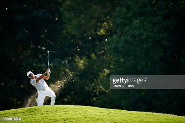 Rickie Fowler of the United States plays an approach shot from the rough on the 14th hole during the first round of the Wyndham Championship at...