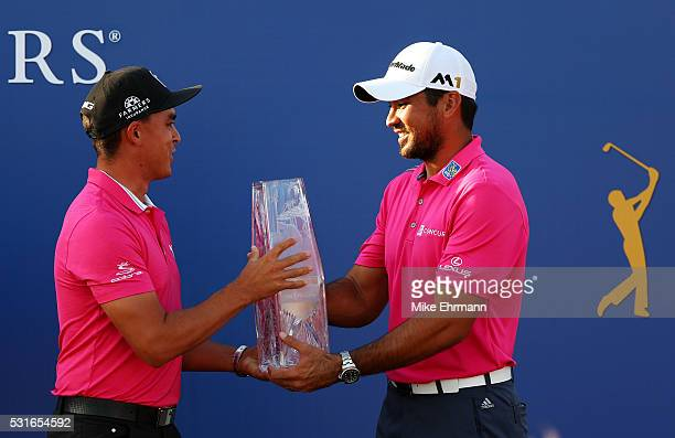 Rickie Fowler of the United States presents the trophy to Jason Day of Australia after Day won the final round of THE PLAYERS Championship at the...