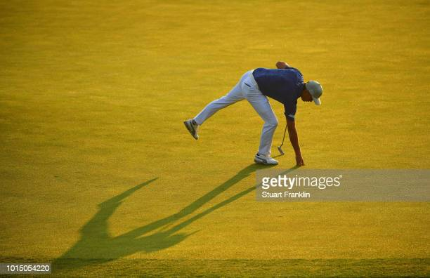 Rickie Fowler of the United States retrieves his ball after making a putt for birdie on the 11th green during the continuation of the weather delayed...