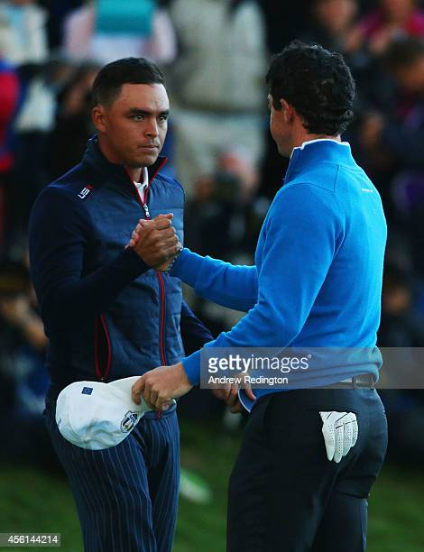 Rickie Fowler of the United States shakes hands with Rory McIlroy of Europe as they halve their match during the Afternoon Foursomes of the 2014...