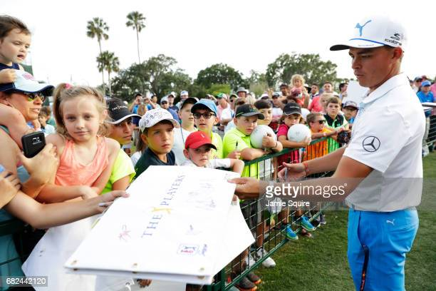 Rickie Fowler of the United States signs autographs after finishing the second round of THE PLAYERS Championship at the Stadium course at TPC...