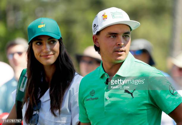 Rickie Fowler of the United States stands with fiancee Allison Stokke during the Par 3 Contest prior to the Masters at Augusta National Golf Club on...