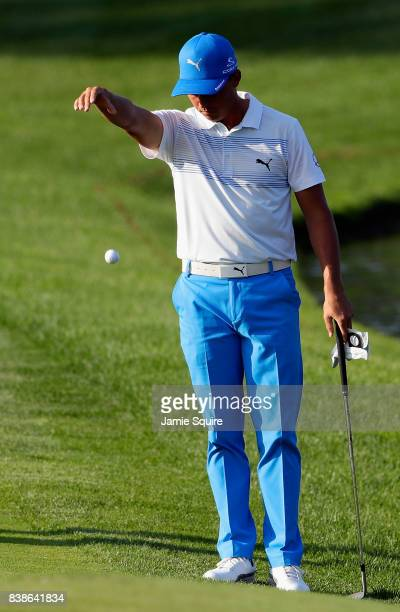 Rickie Fowler of the United States takes a drop after hitting his ball into the water on the 17th hole during round one of The Northern Trust at Glen...