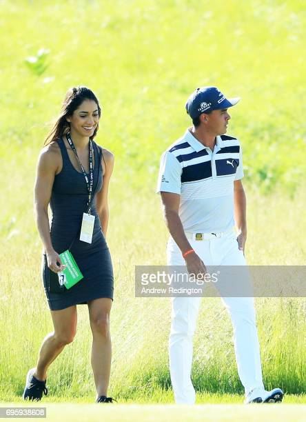 Rickie Fowler of the United States walks along the course with Allison Stokke during a practice round prior to the 2017 US Open at Erin Hills on June...