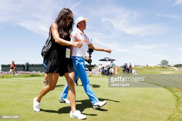 Rickie Fowler of the United States walks from the ninth green with Allison Stokke after finishing during the first round of the 2017 US Open at Erin...