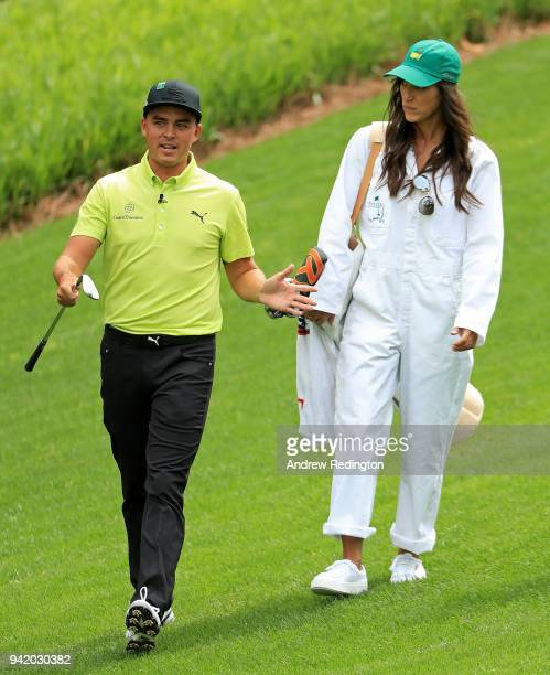 Rickie Fowler of the United States walks with caddie and girlfriend Allison Stokke during the Par 3 Contest prior to the start of the 2018 Masters...