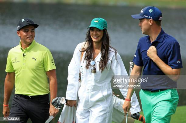 Rickie Fowler of the United States walks with caddie and girlfriend Allison Stokke and Justin Thomas of the United States during the Par 3 Contest...