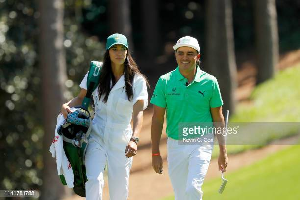 Rickie Fowler of the United States walks with fiancee Allison Stokke during the Par 3 Contest prior to the Masters at Augusta National Golf Club on...